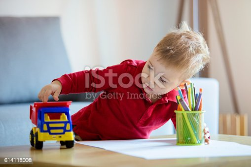 926151996istockphoto Young boy playing with his truck 614118008
