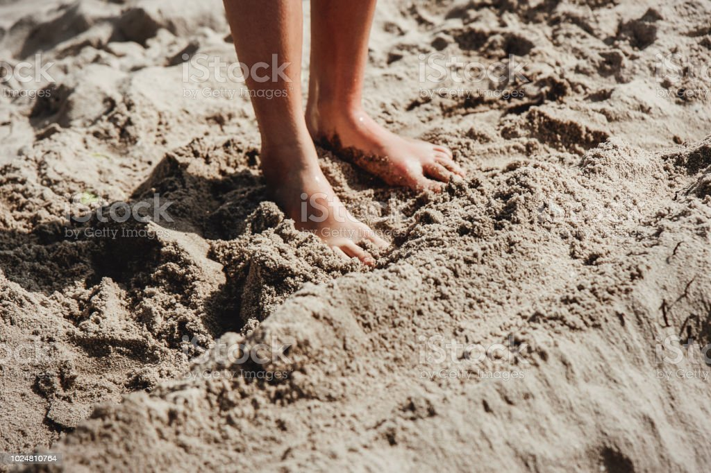 Close up of child feet in the sand. Summer vacations at the beach.