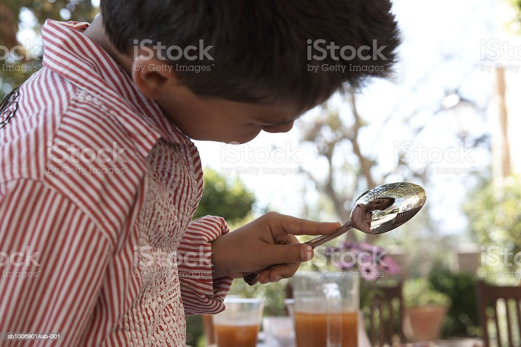 Young boy (8-9) playing with spoon in garden 免版稅 stock photo