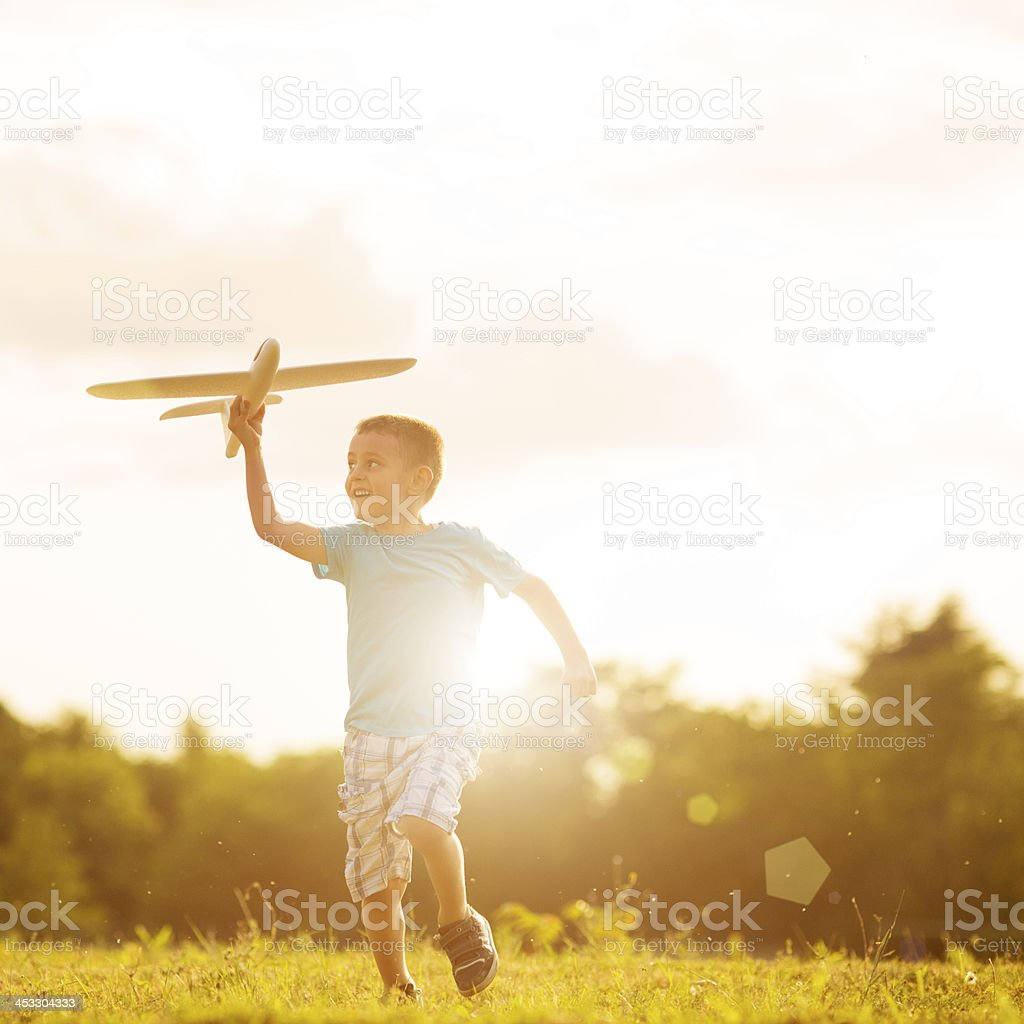 Young boy playing with toy airplane outside stock photo
