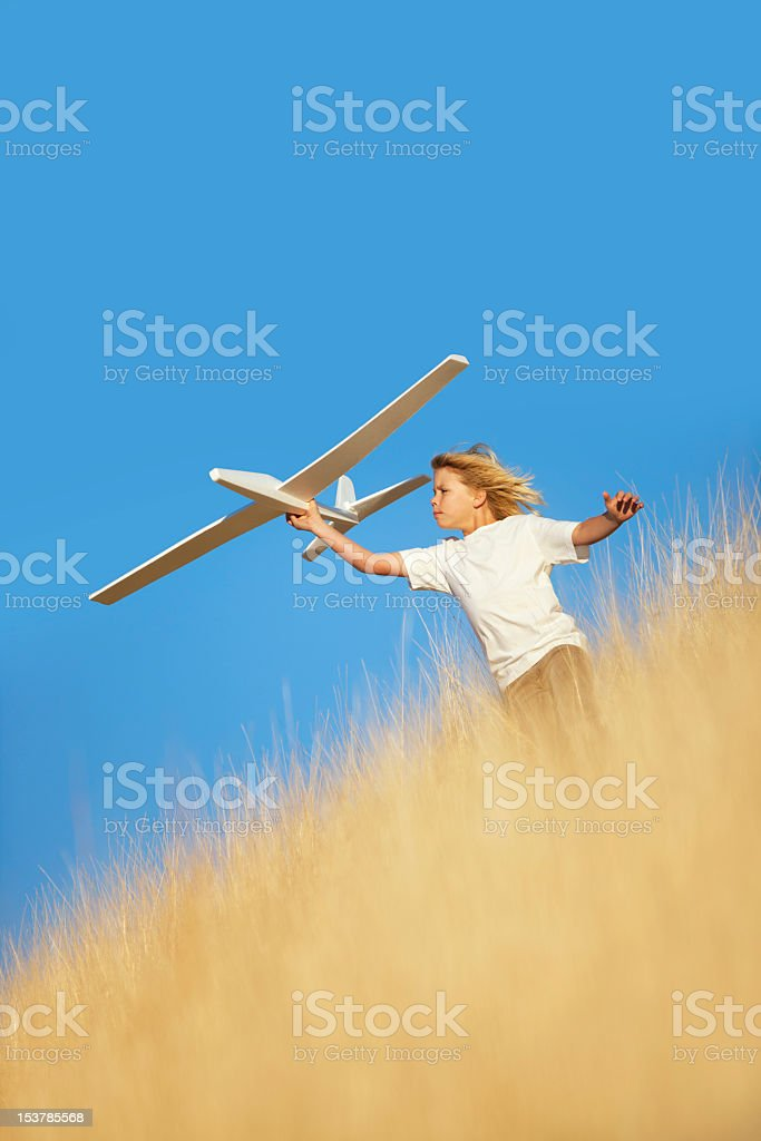 Young Boy Playing with Toy Glider Airplane in Field royalty-free stock photo