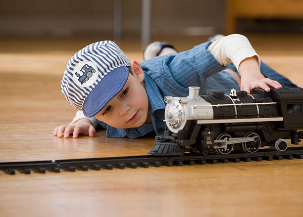 young boy playing with toy trains - transport conductor stock photos and pictures