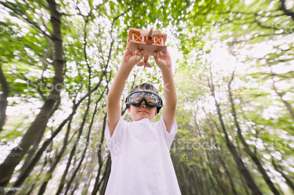 Young boy playing wooden airplane with pilot dressed stock photo