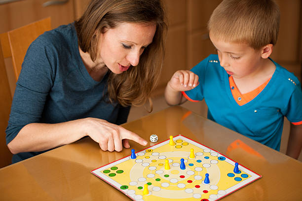 young boy plays ludo game with mother in livingroom - foto de acervo