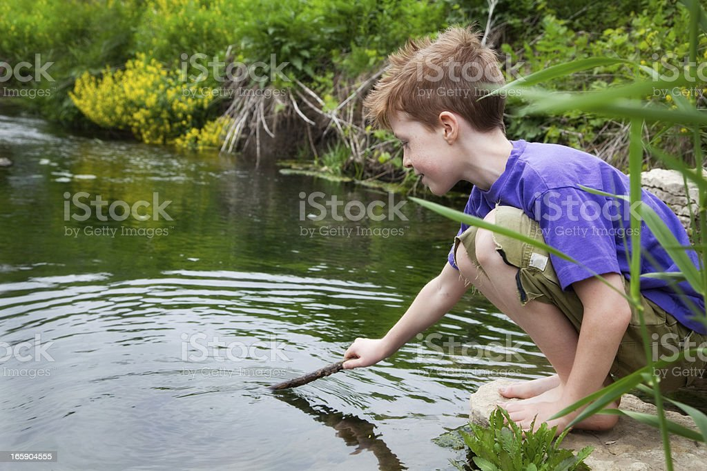 Young boy plays near water and greenery royalty-free stock photo