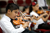 Young violinists play in open concert with the orchestra. Focus on foreground.