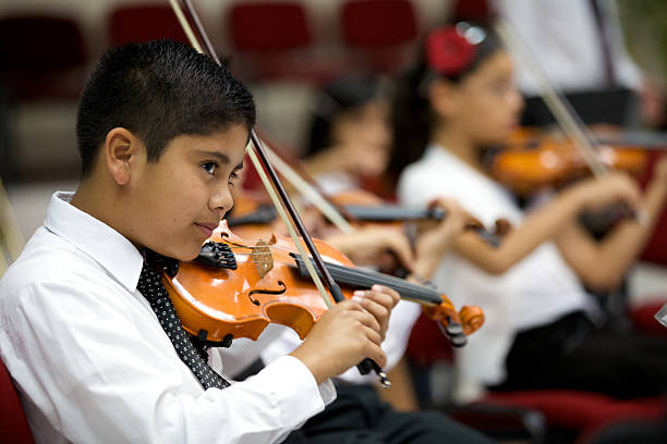 A young boy plays violin and stares outward Young violinists play in open concert with the orchestra. Focus on foreground. string instrument stock pictures, royalty-free photos & images