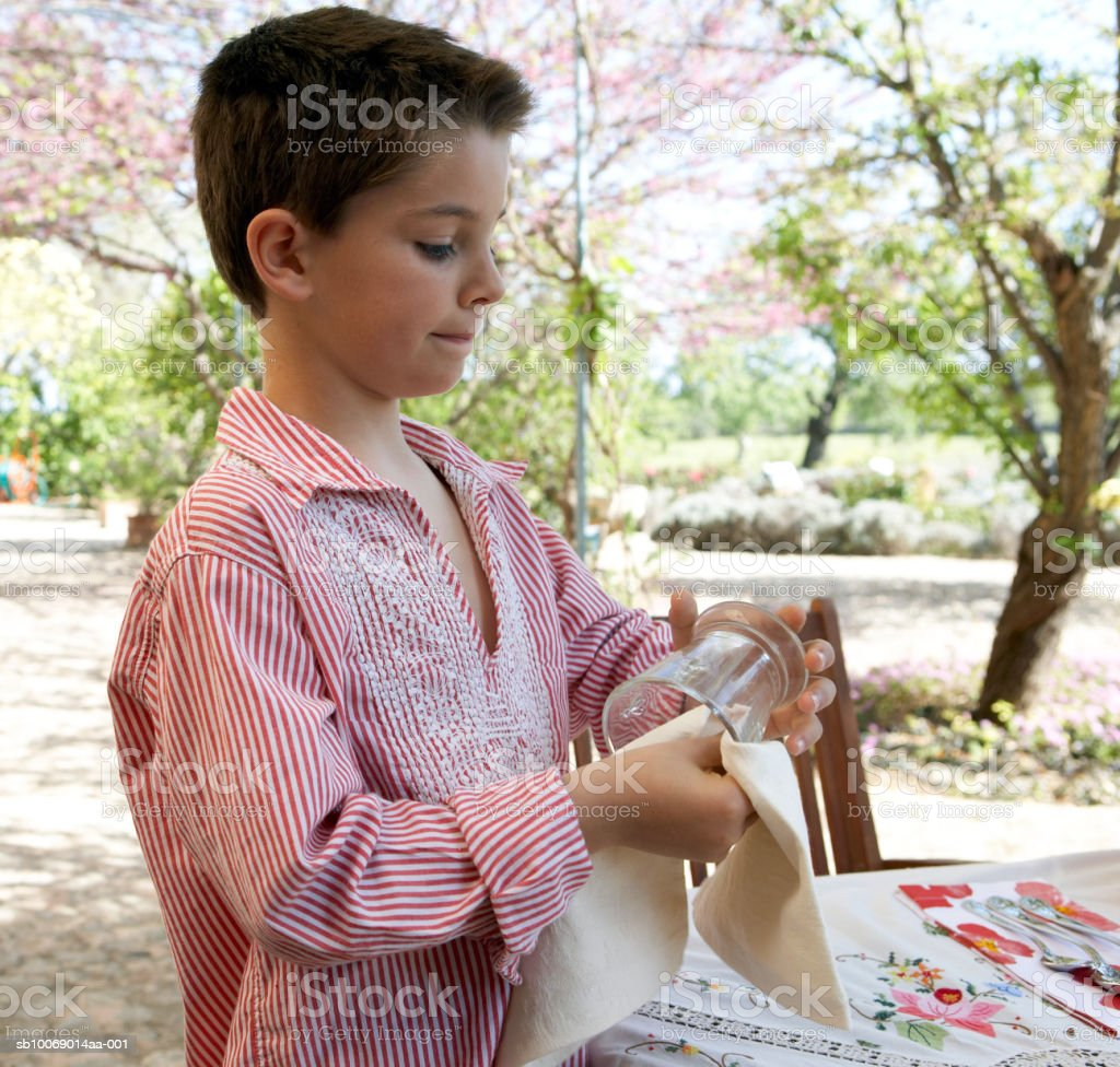 Young boy (8-9) polishing glasses in garden royalty-free stock photo