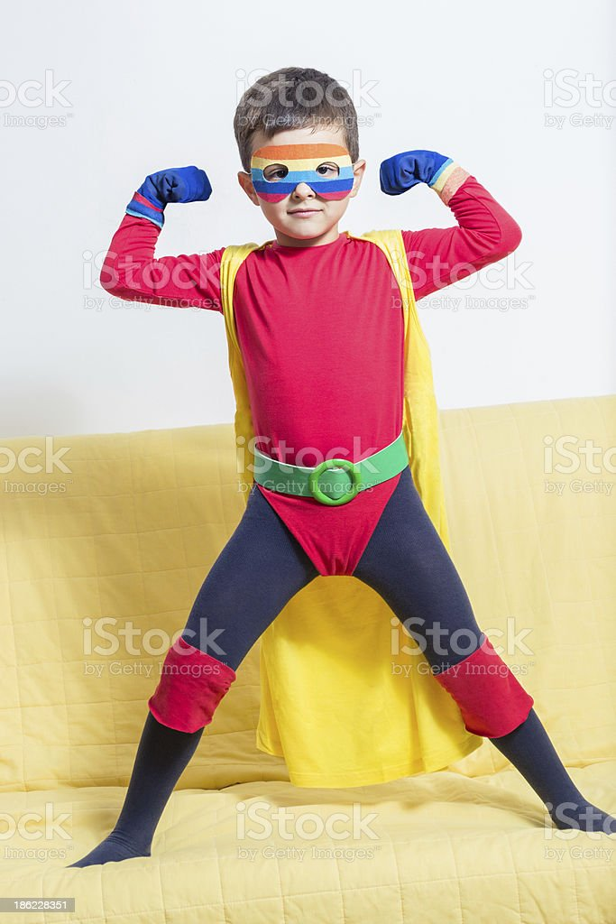 A young boy posed as a superhero with mask and cape  royalty-free stock photo