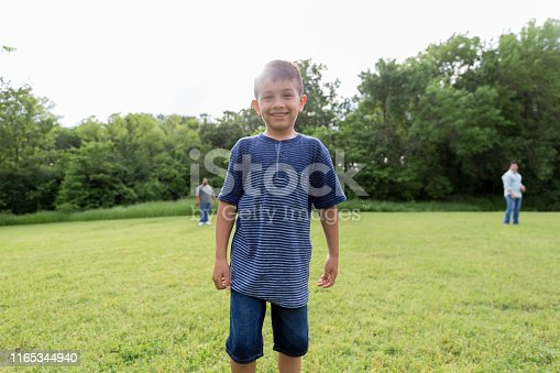 As his uncles play in the background, the elementary age boy poses for the camera.