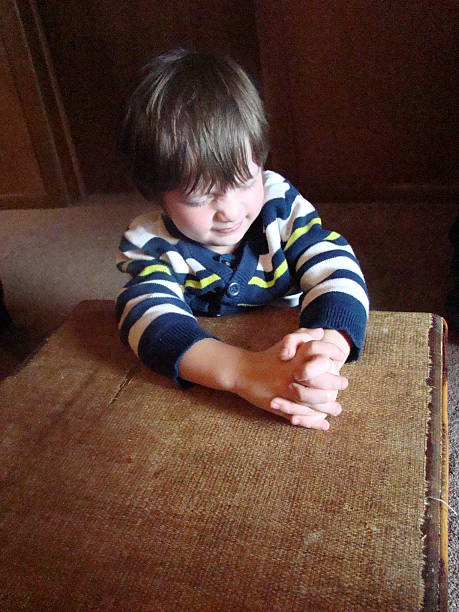 Young boy praying hard  Young boy praying with his eyes closed tightly Amen stock pictures, royalty-free photos & images