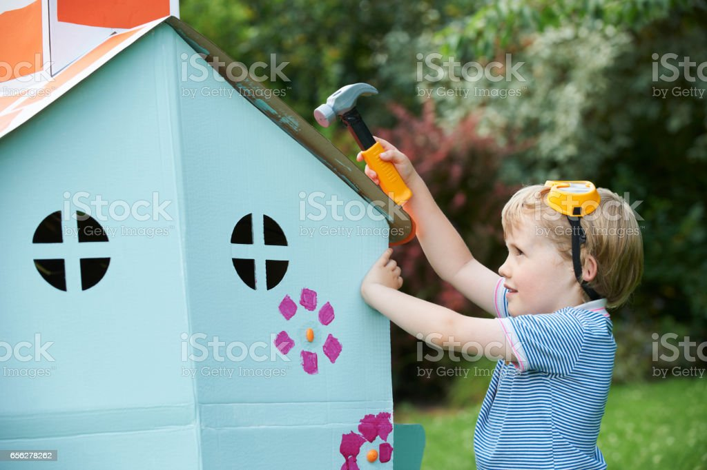 Young Boy Pretending To Fix Cardboard Playhouse stock photo