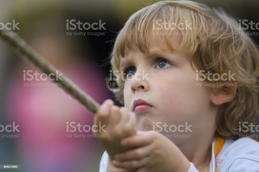 Young Boy Pulling Hard On A Rope Royalty Free Stock Photo