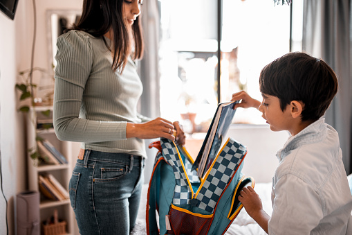 Mother and son in the bedroom. They are packing a backpack for school. He is packing his notebook while the mother is holding a backpack