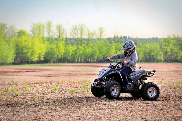 A young boy quading in a spring field A young boy quading in a spring field. quadbike stock pictures, royalty-free photos & images