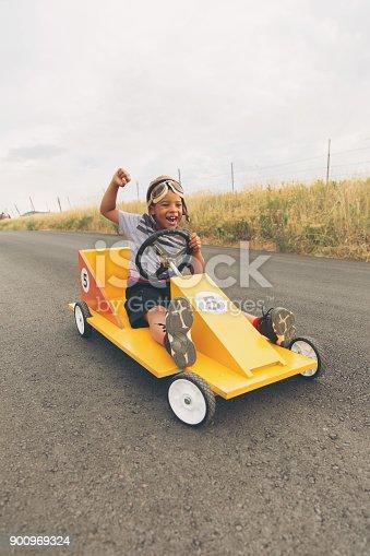 959599892 istock photo Young Boy Racing Homemade Car 900969324