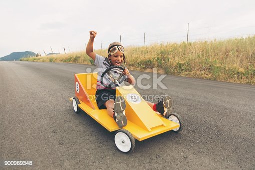959599892 istock photo Young Boy Racing Homemade Car 900969348
