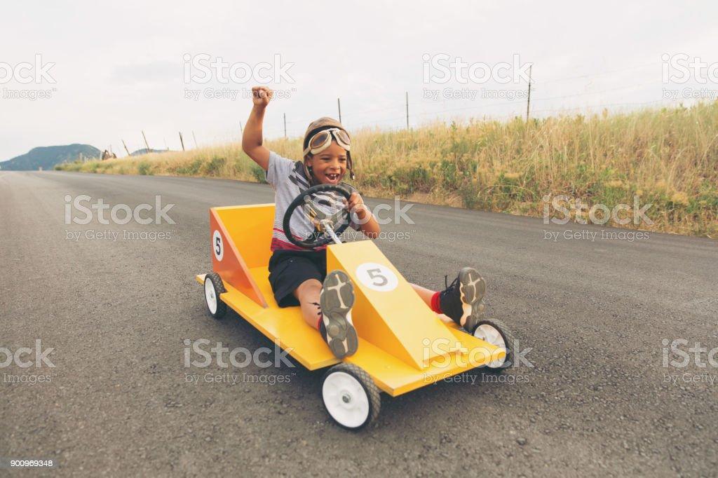 Young Boy Racing Homemade Car stock photo