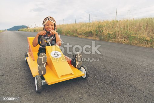 959599892 istock photo Young Boy Racing Homemade Car 900969442