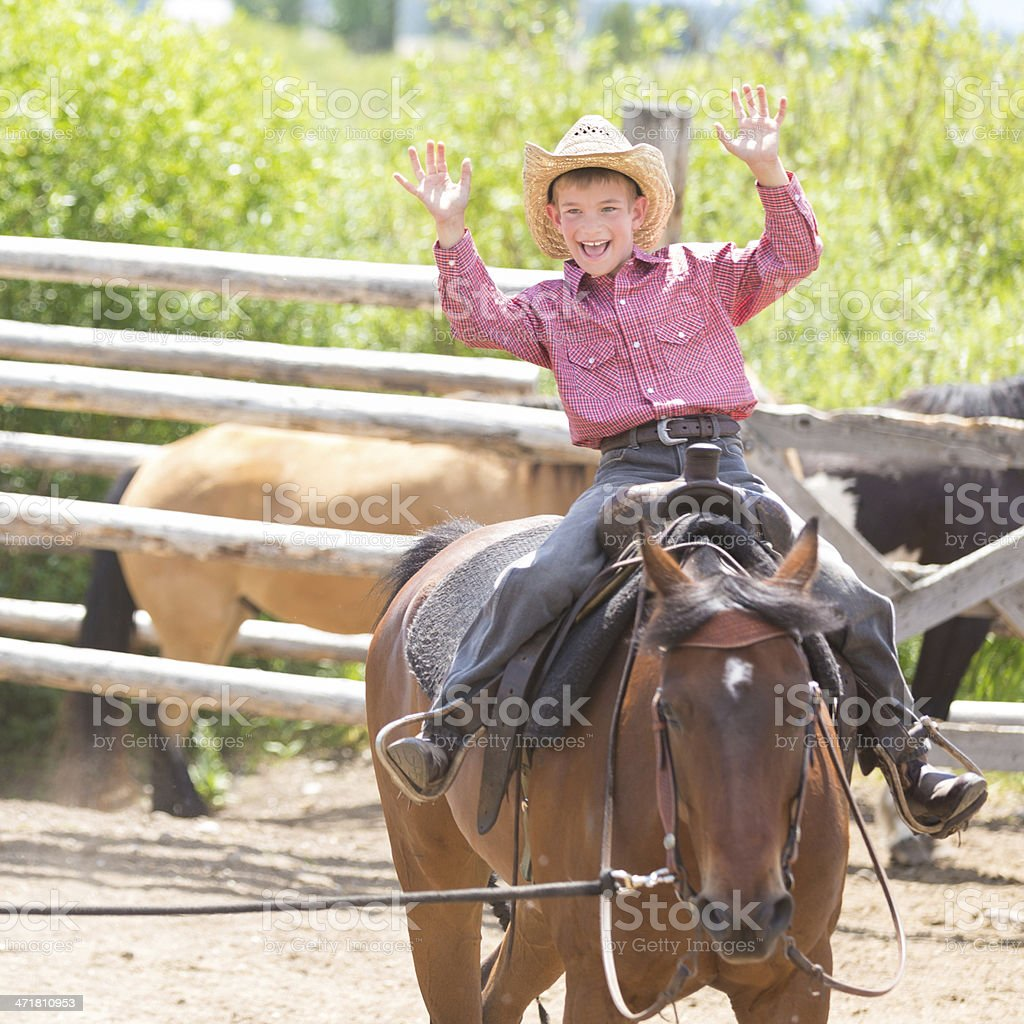 Young boy raising hands in air while riding a horse stock photo