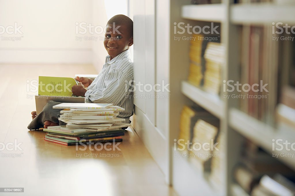 ‡Young boy reading a stack of storybooks stock photo