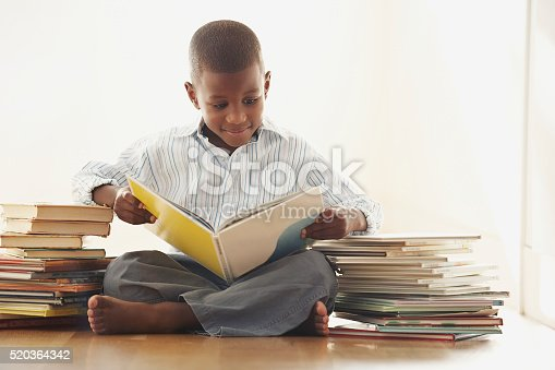 istock Young boy reading a storybook 520364342