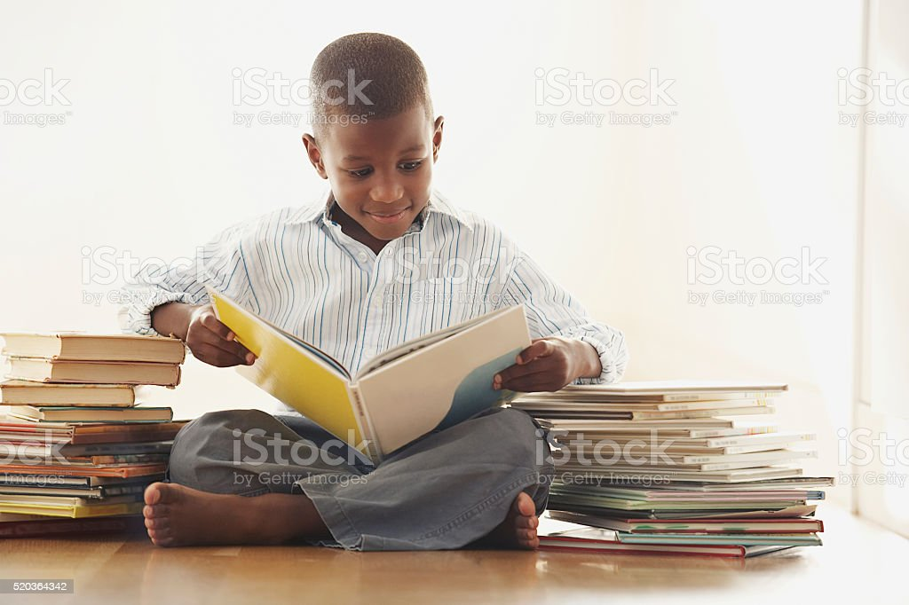 Young boy reading a storybook stock photo