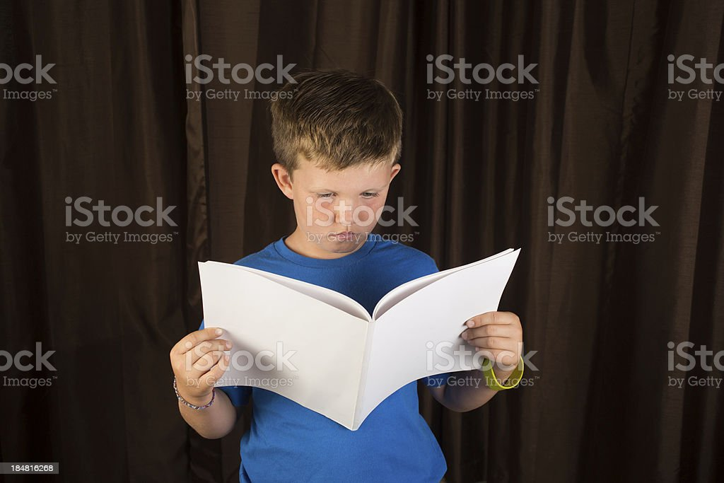 Young Boy Reading Blank Book or Magazine stock photo
