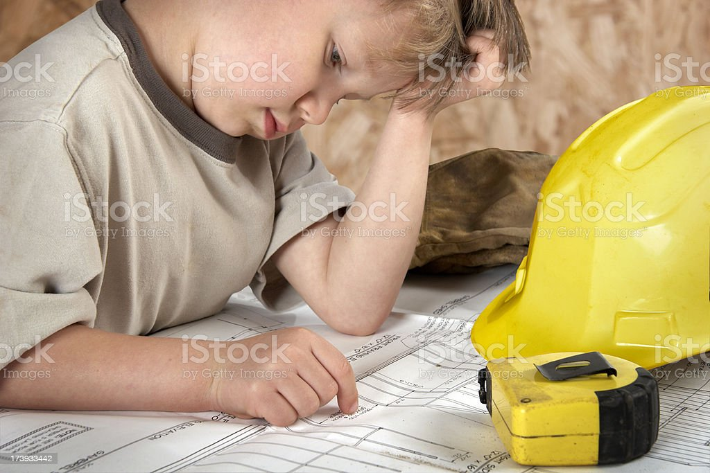 Young boy reading blueprints royalty-free stock photo