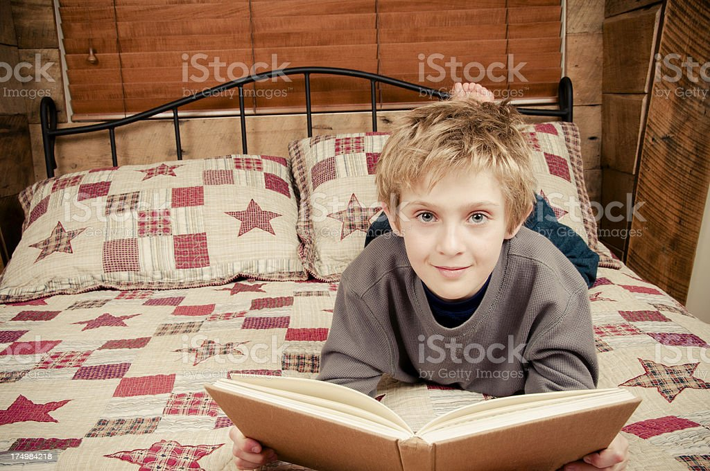 young boy reading while on a bed royalty-free stock photo