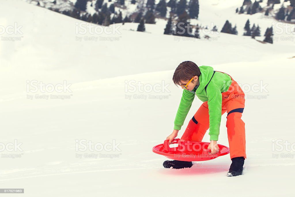 Young boy ready to sledding in the snow stock photo