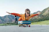 A young boy wearing flying goggles and flight cap has packed his suitcase and has placed it on a skateboard. He is ready to fly away with arms outstretched to the destination of his dreams. Image taken in Utah, USA.