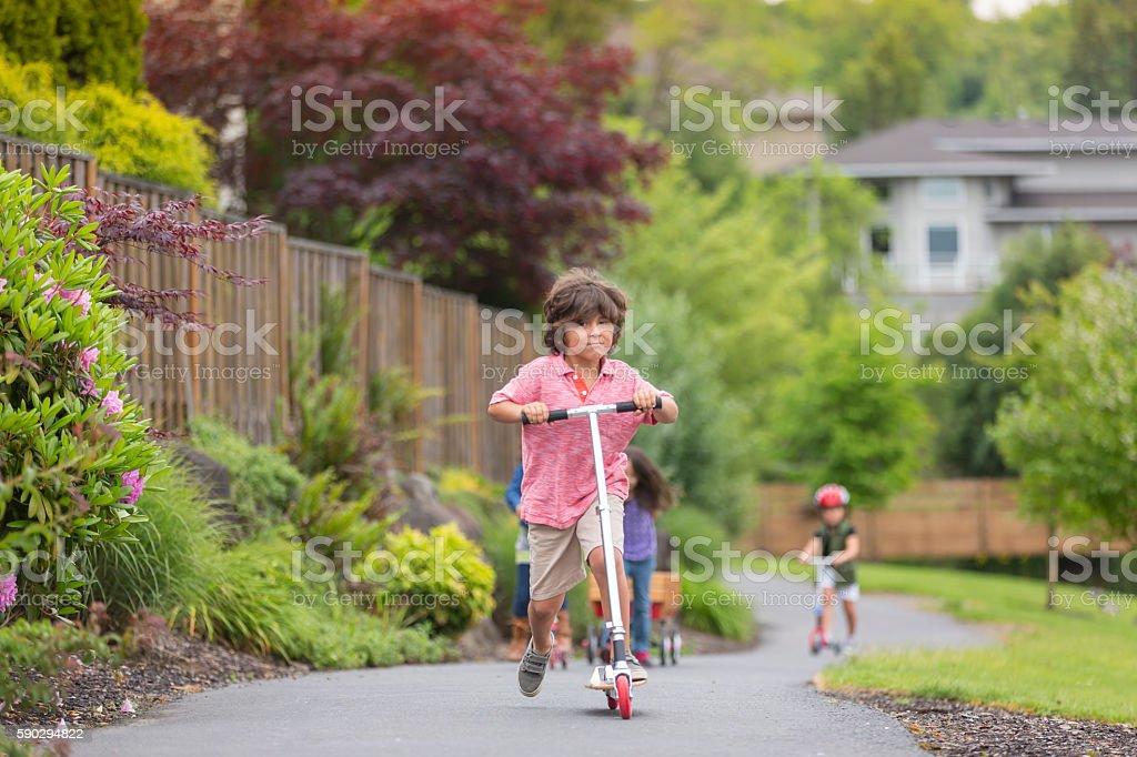 Young boy riding a scooter royaltyfri bildbanksbilder