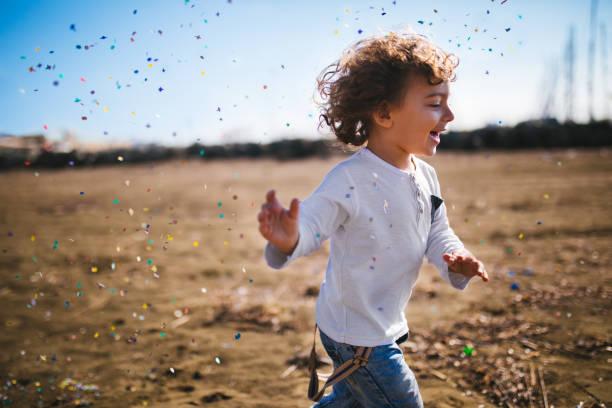 kleiner junge läuft am strand mit konfetti - pailletten shirt stock-fotos und bilder