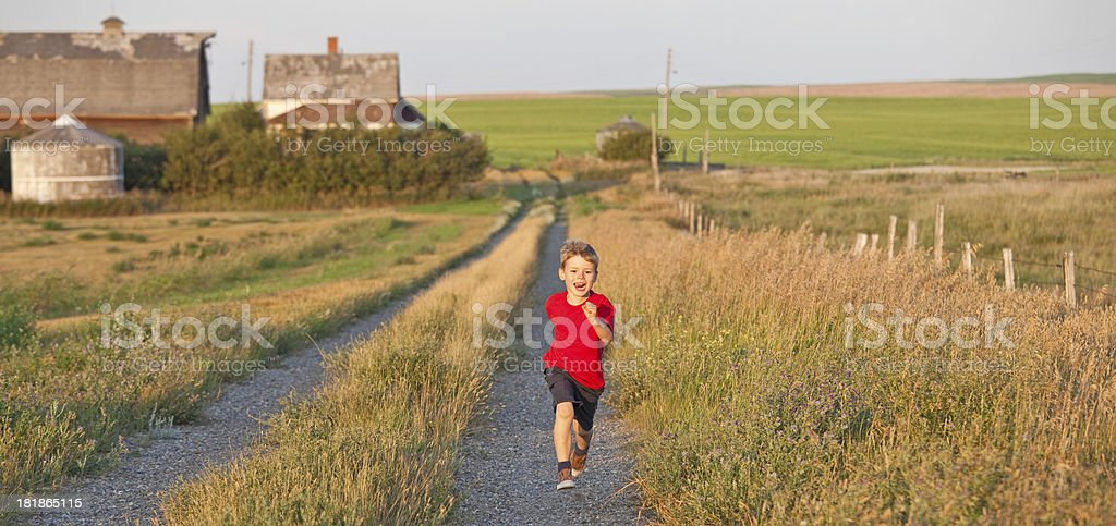 Young Boy Running Down a Country Road royalty-free stock photo