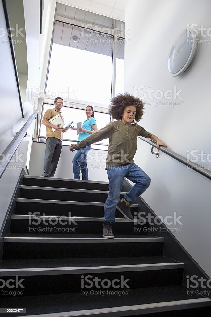 Young Boy Running Down Stairs stock photo