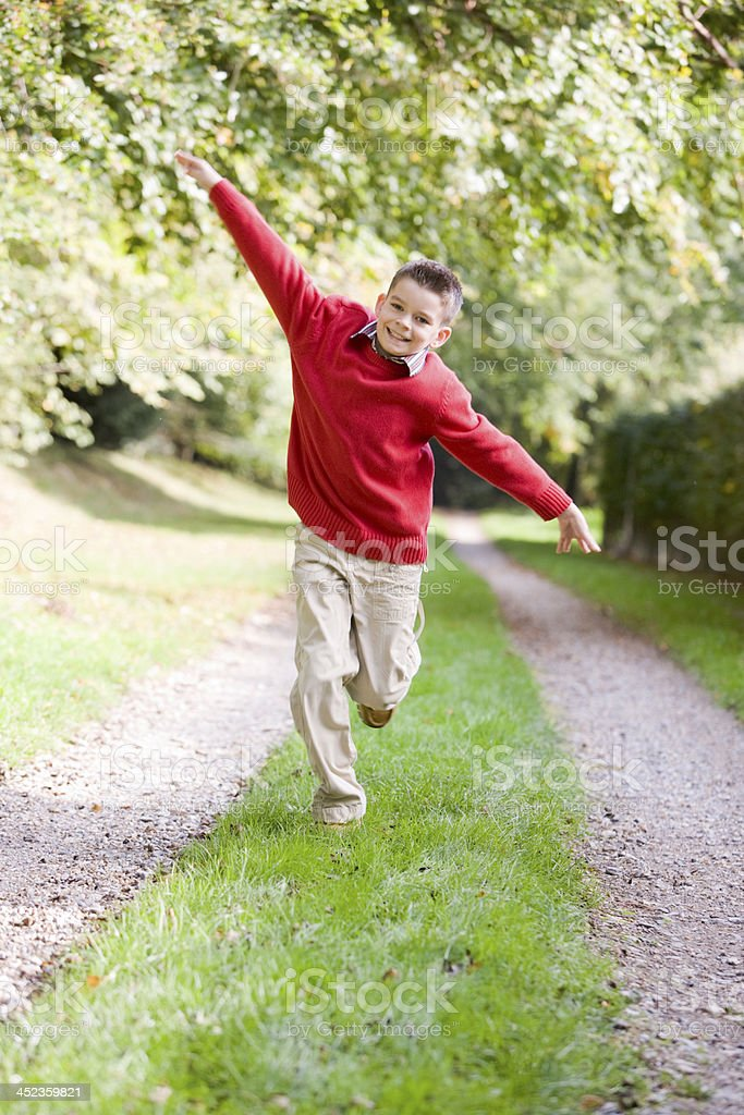 Young boy running on a path outdoors smiling royalty-free stock photo