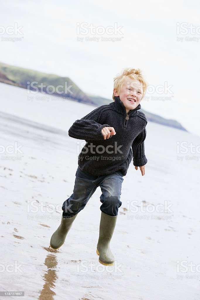 Young boy running on beach smiling royalty-free stock photo