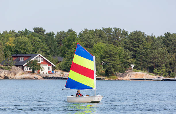 Young boy sailing optimist dinghy in Stockholm Archipelago. Young boy sailing optimist dinghy in Stockholm Archipelago. sailing dinghy stock pictures, royalty-free photos & images