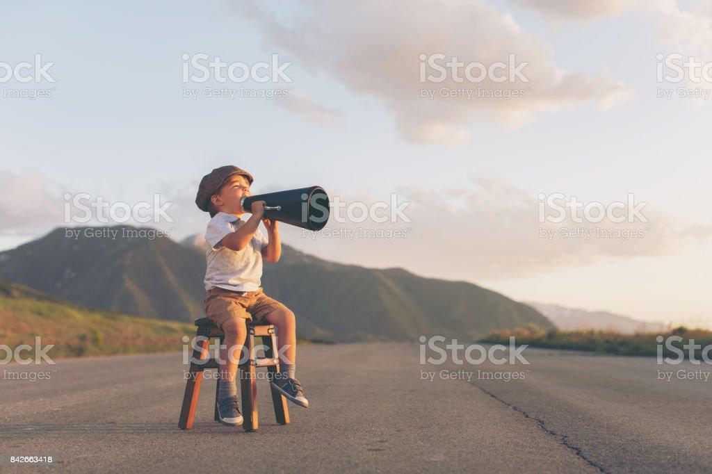 Kleiner Junge Verkäufer gibt gute Nachricht über Megaphon – Foto