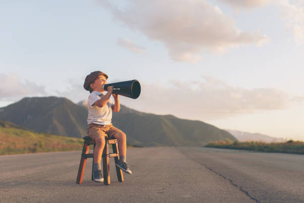 Young Boy Salesman Gives Good News through Megaphone stock photo