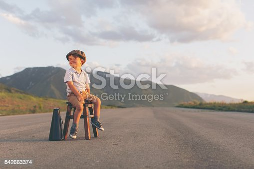 istock Young Boy Salesman Sits on Stool with Megaphone 842663374