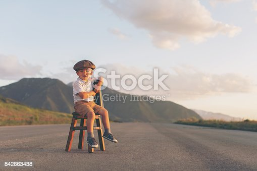 istock Young Boy Salesman Sits on Stool with Megaphone 842663438
