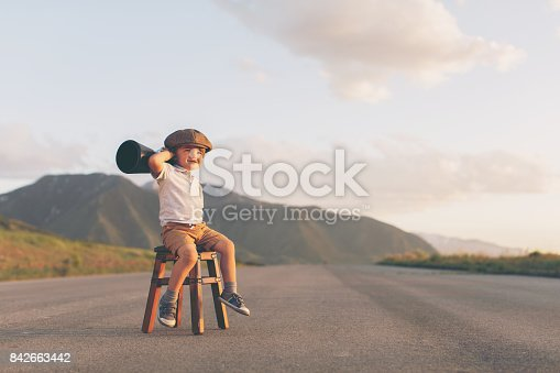 istock Young Boy Salesman Sits on Stool with Megaphone 842663442