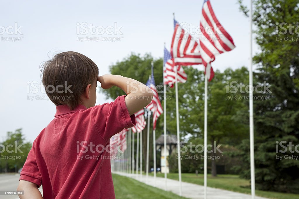 Young boy salutes flags of Memorial Day display stock photo