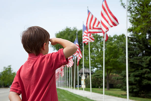 young boy salutes flags of memorial day display - memorial day stok fotoğraflar ve resimler
