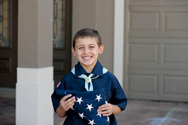 young boy scout con bandera estadounidense - boy scout fotografías e imágenes de stock