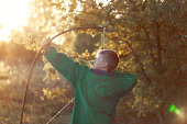 Young boy, shoot with handmade bow and arrow at target on sunset, summertime outdoor.