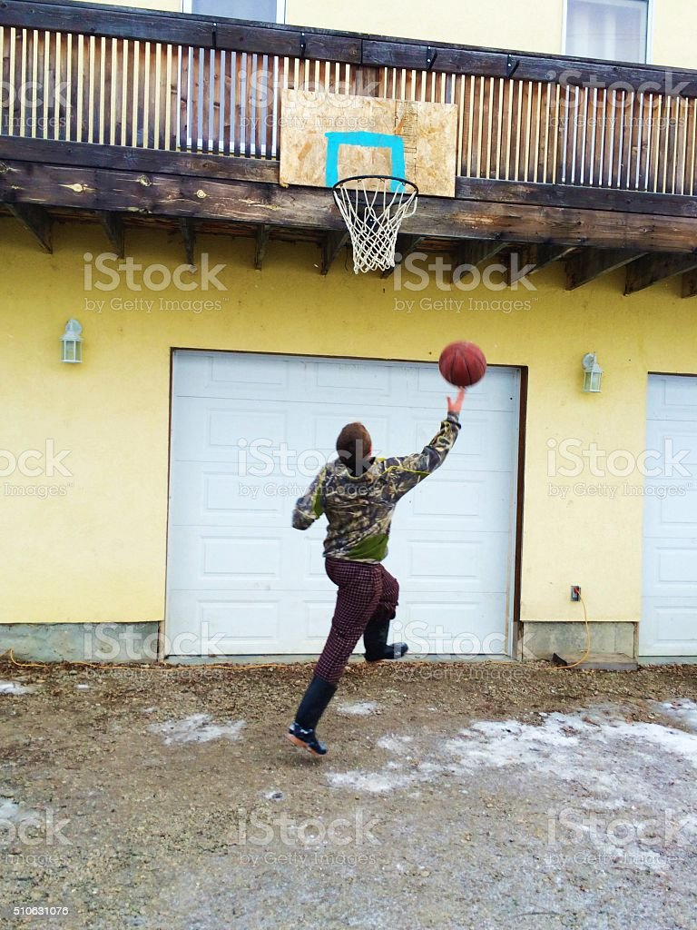 young boy shooting a basketball stock photo
