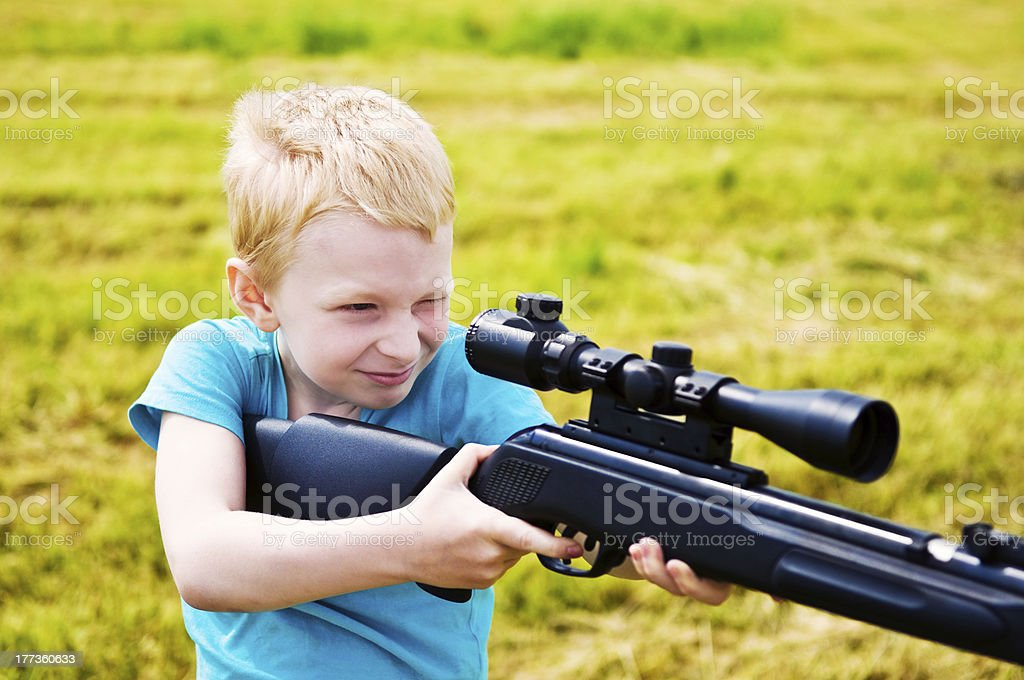 young boy shooting stock photo